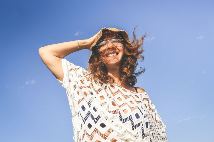 Low angle view of woman wearing hat against sky