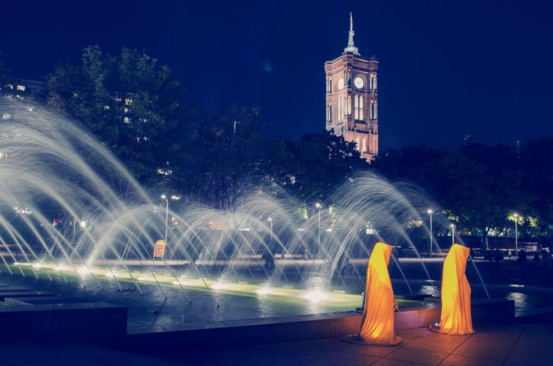 Four monks from the Festival of Lights in Berlin Berlin Festival Of Lights Light Festival Night Rotes Rathaus Berlin Tower Clock Clock Tower Fountain Water Monks Tree Orange Clothes Trees Darkness