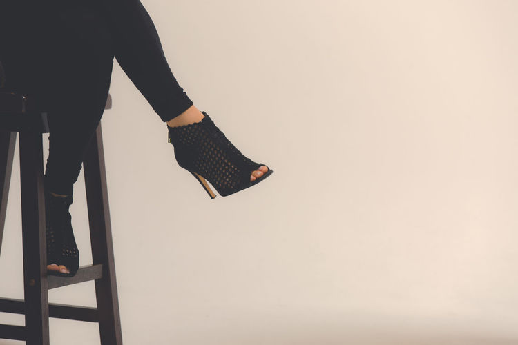 Low section of woman wearing high heels while sitting on stool against wall