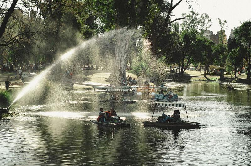 People enjoying in lake against trees