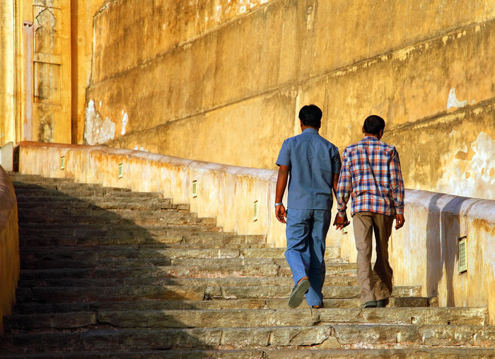 Rear view of men moving up steps at amer fort