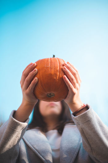Autumn Mood One Person Real People Leisure Activity Food And Drink Lifestyles Front View Holding Orange Color Casual Clothing Sky Day Unrecognizable Person Food Focus On Foreground Healthy Eating Close-up Copy Space Human Hand Headshot Hand Obscured Face Finger
