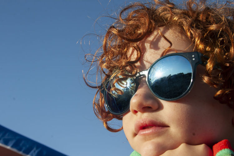 Close-up of girl wearing sunglasses against sky