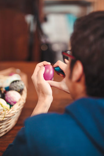 Close-up of man decorating easter egg at home