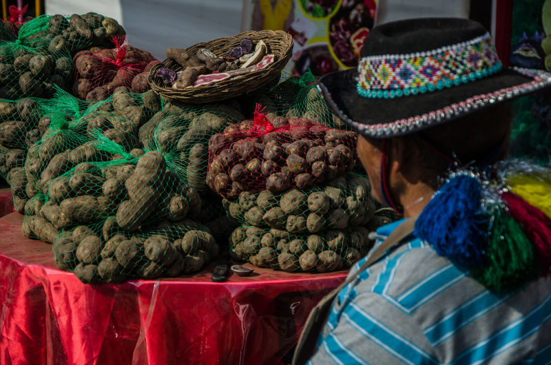 Seller seeing his small potatoes called: Native potatoes, in Lima - Peru Andes Local Market Native Natural Peru South Tradition Travel Typical Work America Authentic Colorful Colour Food Fruit Indigenous  Peruvian Potatoes Product Sacredvalley Tourism Traditional Urubamba