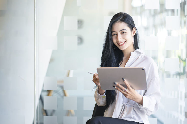 Portrait of smiling young businesswoman holding digital tablet