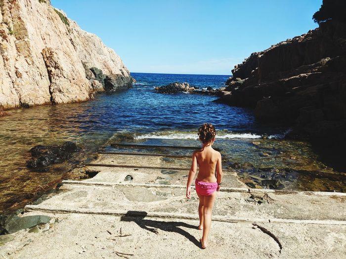 Rear view of girl walking by sea