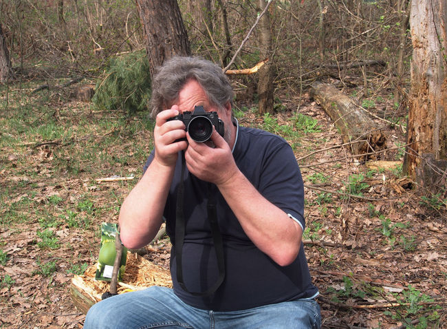 Man With a camera in the spring forest. Camera Activity Camera - Photographic Equipment Casual Clothing Day Digital Camera Field Forest Forest. Front View Holding Land Leisure Activity Lifestyles Nature Obscured Face One Person Outdoors Photographer Photographing Photography Themes Plant Real People Spring Technology Tree