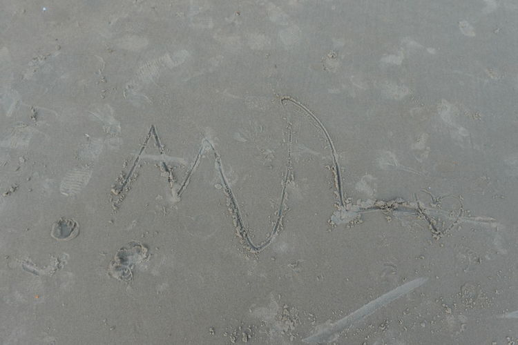 High angle view of text on wet sand