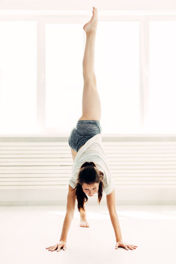 Young beautiful girl doing warm-up contemporary at home Indoors  Woman Home Home Interior Interior Sportsman Dance Contemporary Girl Sexygirl Morning Light Window Plant Stretching Young Happy Females Room Lifestyles Dancing Beauty Beautiful Pretty Modern