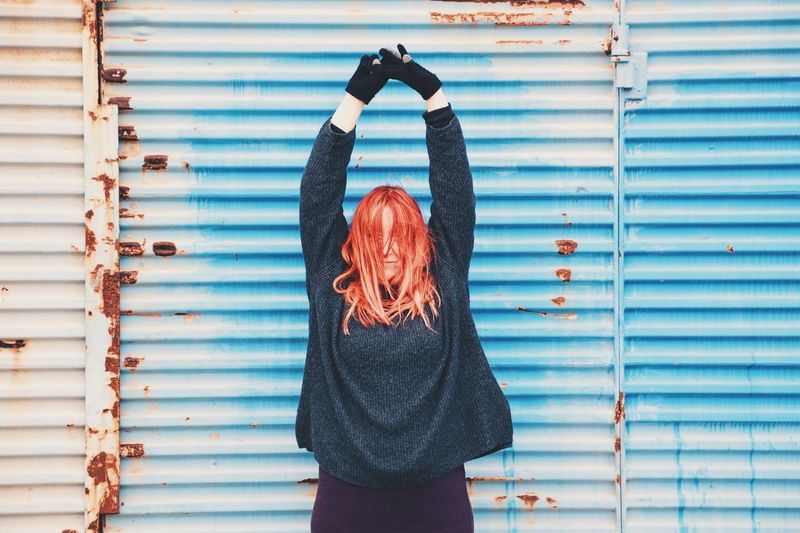 Woman Standing With Arms Raised Against Blue Weathered Shutter