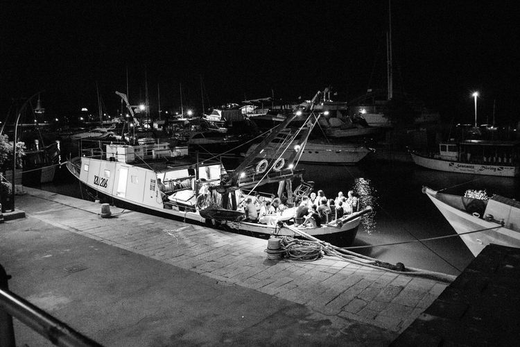 People on pier at harbor against sky at night