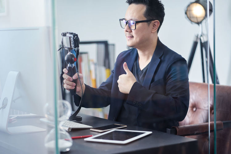 Businessman holding camera while sitting at office