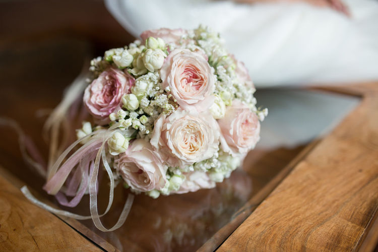 Close-up of bouquet on glass table during wedding