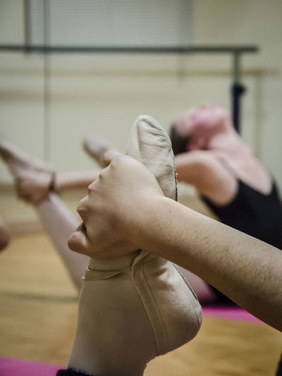 Close-Up Of Ballet Dancer Stretching In Studio