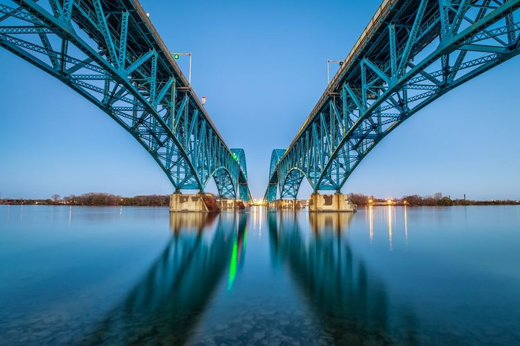 Low angle view of bridge over river against clear sky during sunset