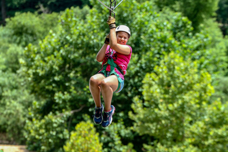 Fun Adventure Day Excitement Extreme Sports Freedom Full Length Hanging Helmet Leisure Activity Lifestyles Motion Nature One Person Outdoors Plant Protection Real People Rope Safety Safety Harness Sport Tree Zip Line