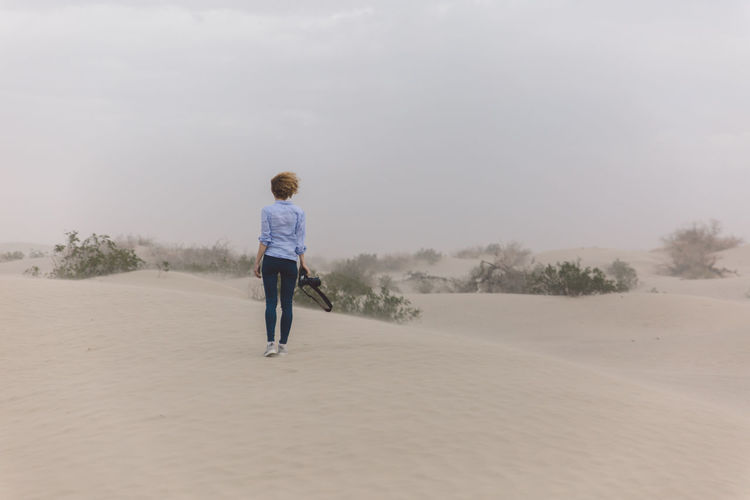 Arid Climate Arid Landscape Beauty In Nature Casual Clothing Curly Hair Day Death Valley Death Valley National Park Desert Dunes Full Length Girl Landscape Leisure Activity Lifestyles Nature Nature One Person Outdoors Real People Rear View Sky Standing Tree Walking Modern Workplace Culture