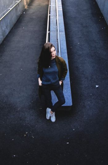 High angle view of young woman standing on road in city