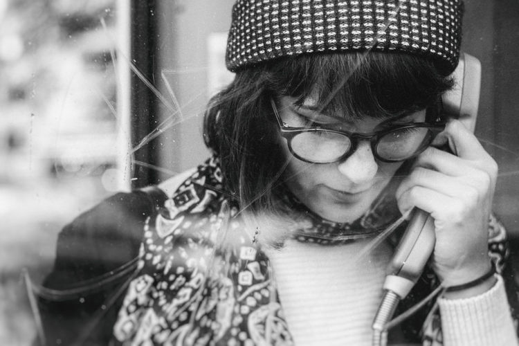 Close-up of young woman talking in telephone booth