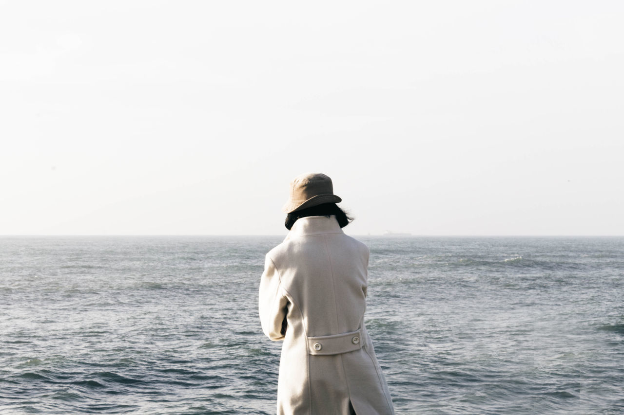 Rear view of person in long coat standing by sea against sky