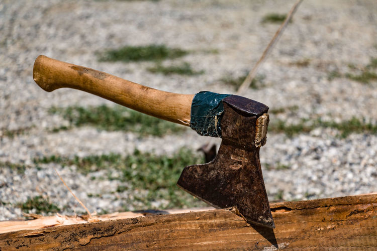Close-up of axe in wooden plank