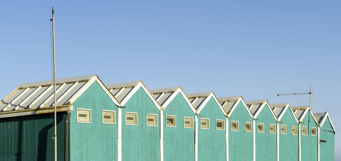 Beach huts against clear blue sky