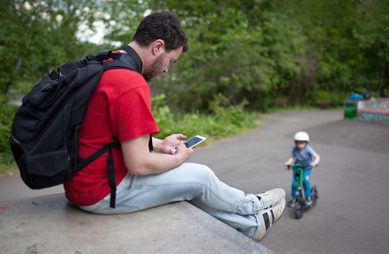Rear view of man using mobile phone while sitting on tree