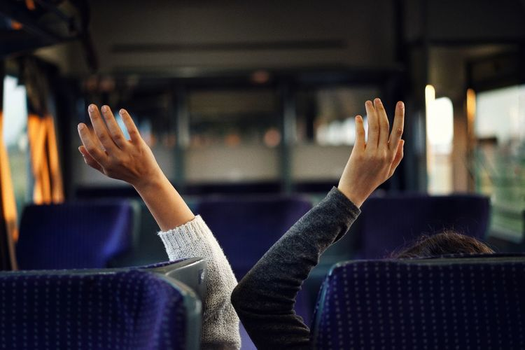 Cropped image of people with arms raised in bus