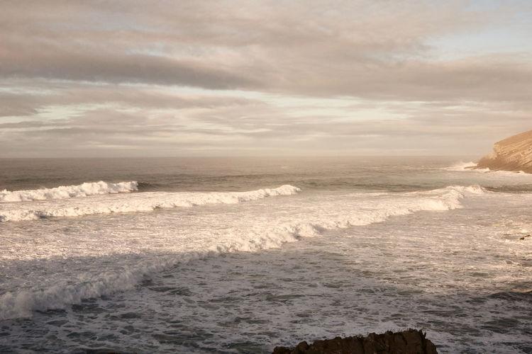 Waves rushing towards shore against sky