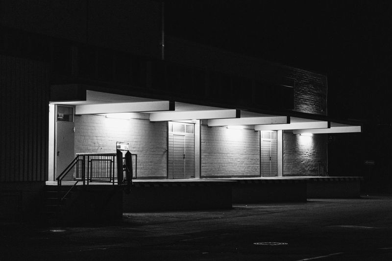 Empty parking lot against building at night