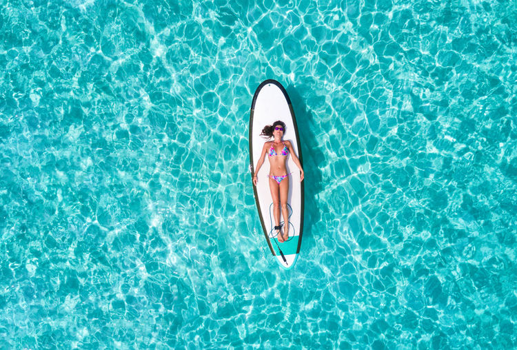 Aerial view of woman in bikini lying on surfboard over sea