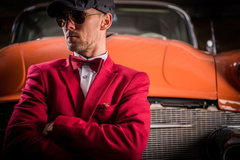 Man standing against vintage orange car