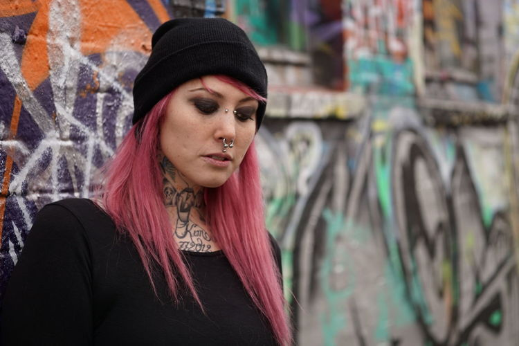Alternative Authentic Casual Clothing Emo Girl Graffiti Inked Lifestyles Looking Down Lost In Thought Person Pierced Piercing Pink Hair Punk Real People Serious Street Tattoo Tattooed Urban Woman Young Adult Young Women Youth