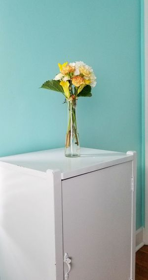 Close-up of white flower vase on table against wall