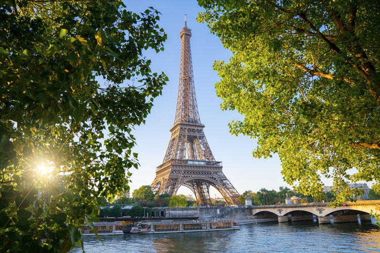 Low Angle View Of Eiffel Tower By River Amidst Trees Against Sky