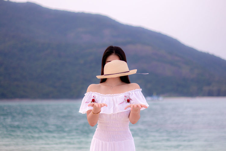 Young woman levitating hat while standing at beach