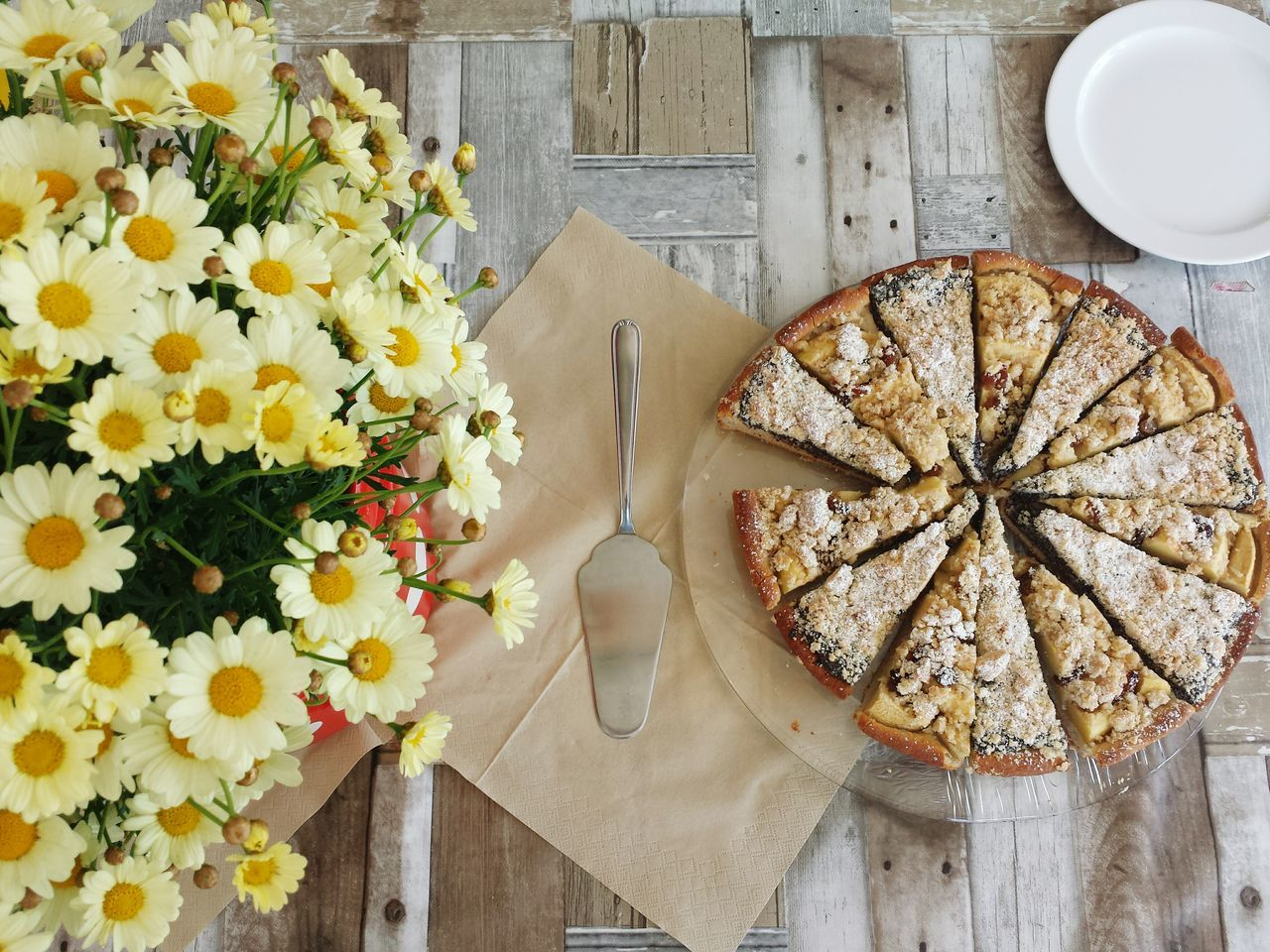 High angle view of flowers and tart on wooden table