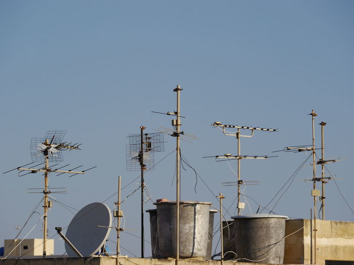 Low angle view of antenna against clear sky