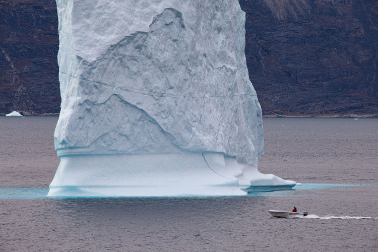 Scenic view of iceberg and boat
