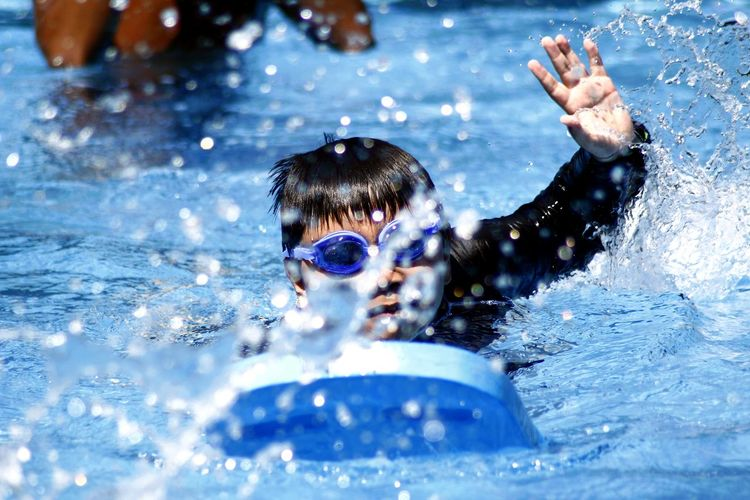 Close-up of boy with kickboard swimming in pool
