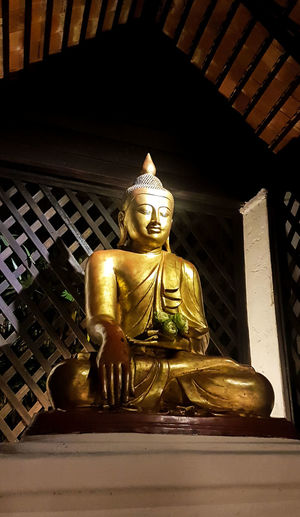 What a presentation in the early evening Architecture Budda Statue Buddah Culture Day Flower Flower In Hand God Gold Gold Colored Human Representation Idol Indoors  Low Angle View Male Likeness No People Place Of Worship Podium Religion Religious Sculpture Sculpture Side View Spirituality Statue Temple