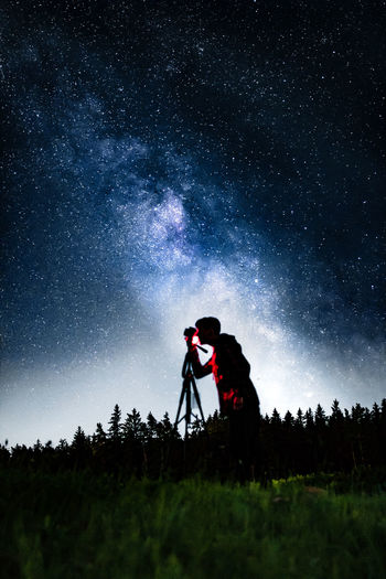 Silhouette man photographing on field against sky at night