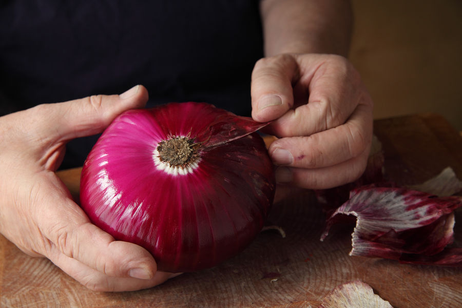 A man peels off an outer layer of a large red onion Allium Copy Space Hands Natural Light Textures Black Tshirt Casual Clothing Close-up Fingers Food Food Preparation Freshness Holding Indoors  Men Onion Skin Peeling People Real People Room For Text Root Vegetable Studio Shot Vegetable