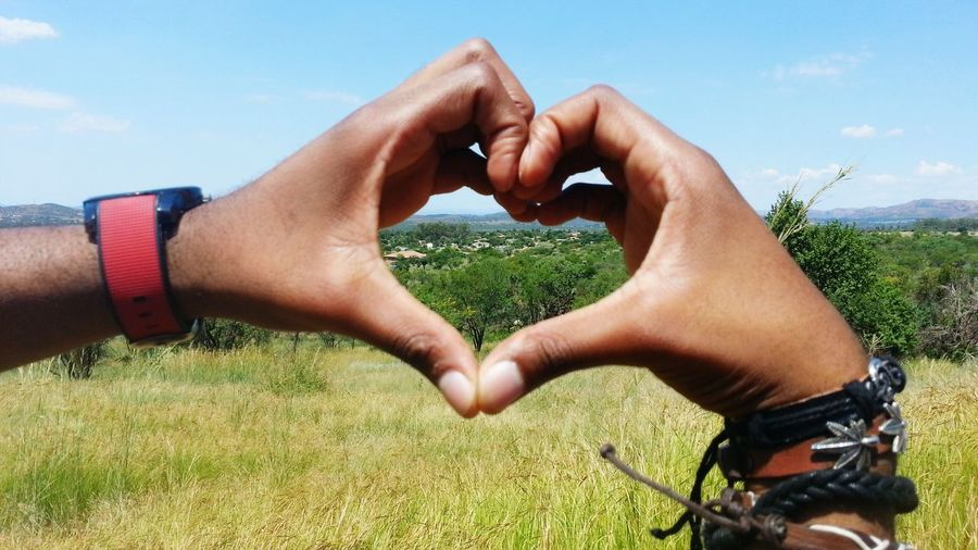 Cropped image of hands making heart shape against field