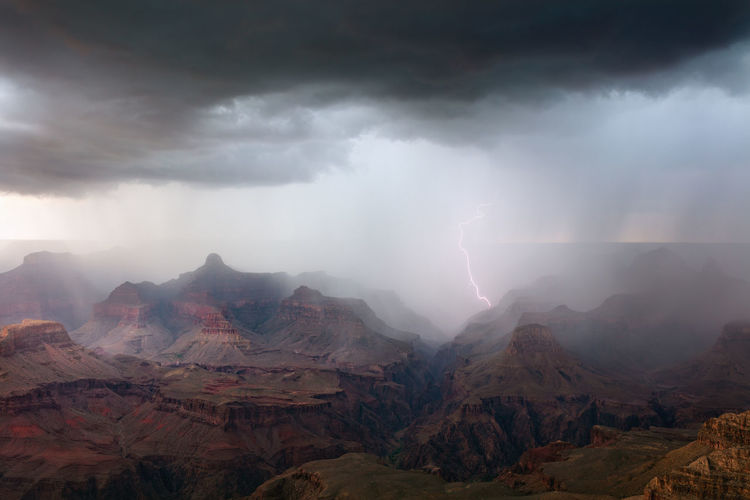A dramatic thunderstorm with lightning sweeps across the grand canyon.