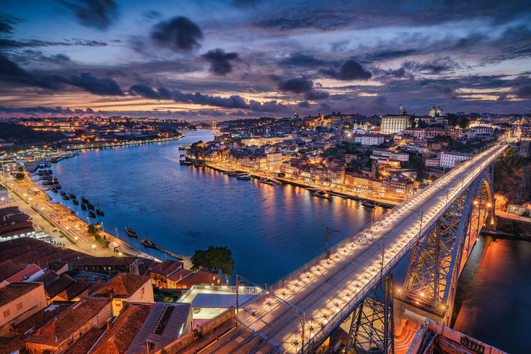 High angle view of illuminated city by river at sunset