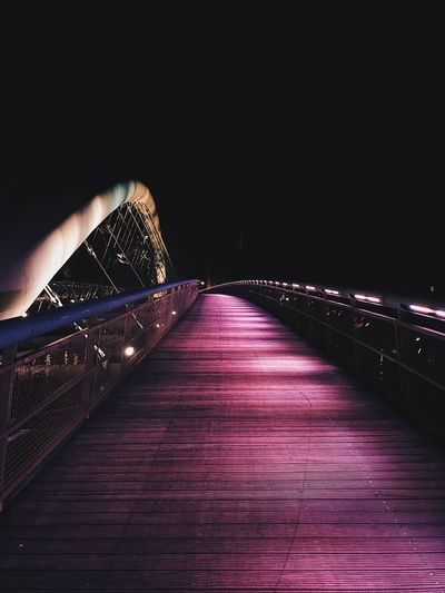 Illuminated footbridge against sky at night