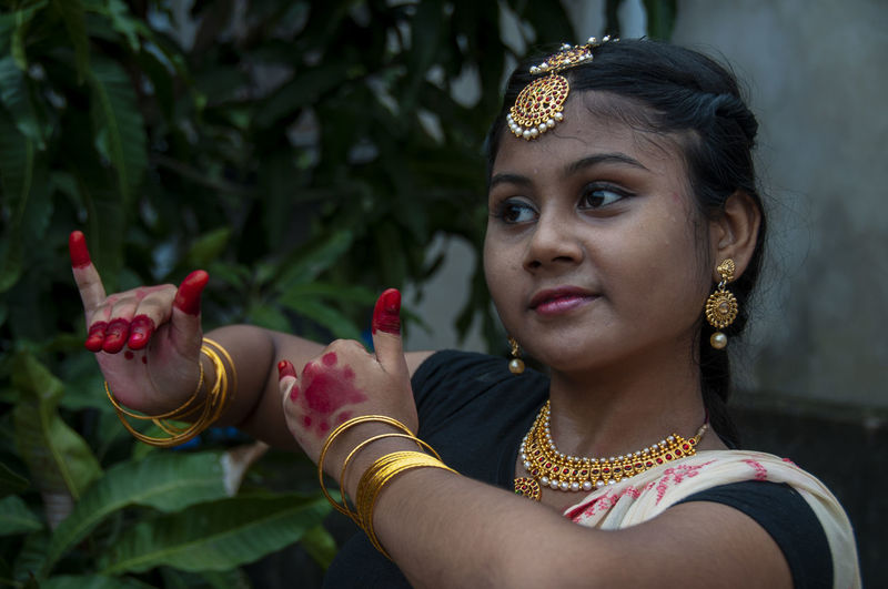 A teenage girl practicing bharatnatyam in nature