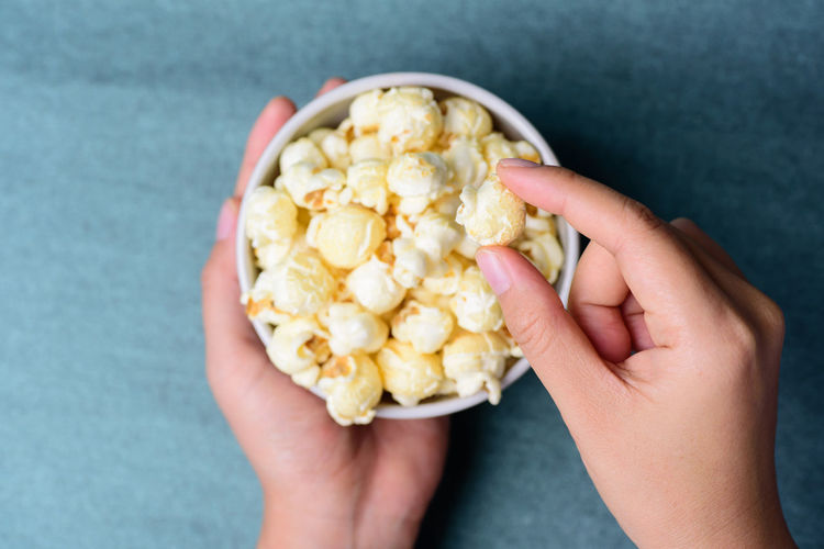 Cropped hand holding popcorn